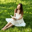 Portrait of attractive young girl reading book in beautiful sunshine — Foto de Stock