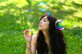 Portrait of attractive young girl inflating colorful soap bubble — Stock Photo