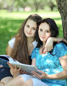 Beautiful mother and daughter reading fairy book in summer park — Stockfoto