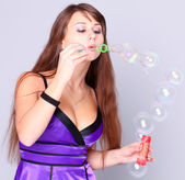 Portrait of funny lovely teenage girl inflating colorful soap bubbles, stud — Stock Photo