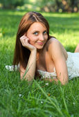 Pretty young girl relaxing on the lawn — Stock Photo