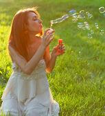 Atraktivní mladá dívka s mýdlovými bublinami — Stock fotografie