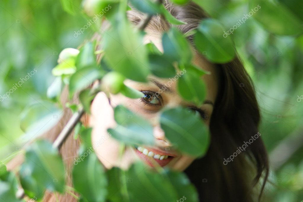 Portrait of beautiful young woman concealing in summer park — Stock Photo #6963601