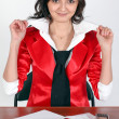 Portrait of beautiful young lady boss sitting in bright red uniform — Stock Photo
