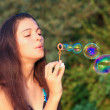Pretty woman inflating soap-bubbles — Stock Photo #6970318