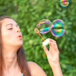 Pretty woman inflating soap-bubbles — Stock Photo #6970328