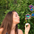Pretty woman inflating soap-bubbles — Stock Photo