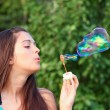 Portrait of attractive young girl inflating colorful soap bubbles outdoor — Stock Photo #6970332