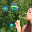 Pretty woman inflating soap-bubbles — Stock Photo #6970333