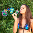 Portrait of attractive young girl inflating colorful soap bubbles outdoor — Stock Photo #6970334