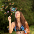 Portrait of attractive young woman in beautiful swimsuit inflating soap bub - Stock Photo