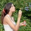 Attractive girl blowing soap bubbles - Stock Photo