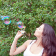 Attractive girl blowing soap bubbles — Stock Photo