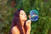 Portrait of attractive young girl inflating colorful soap bubbles outdoor — Stock Photo