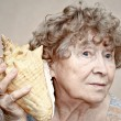 Smiling great grandmother listening to a seashell — Stock Photo