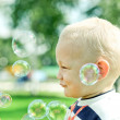 Happy child inflating soap bubbles - Stock Photo