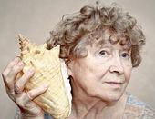 улыбаясь прабабушка слушать раковины — Стоковое фото