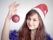 Attractive young girl with christmas presents wondering — 图库照片