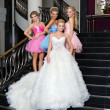 The bride with her bridesmaids on the stairs — Stock Photo #7632240