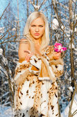 Beautiful blonde with naked shoulders in the winter forest — Stock Photo