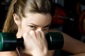 Beautiful woman who exercising with dumbbells in the sport club. — Stock Photo