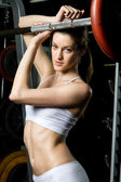 Beautiful woman is doing exercises with barbell in the sport club. — Стоковое фото