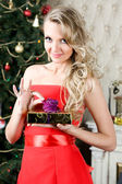 Beautiful woman with gift box at the Christmas tree. — Stok fotoğraf