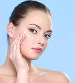 Teen girl applying cream on skin around eyes — Stock Photo