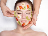 Cosmetician doing fruit mask on a face of woman — Stock Photo