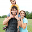 Happy young family posing outdoors — Stok fotoğraf