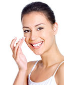 Smiling woman applying moisturizer cream — Stock Photo