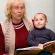 Grandmom reading to her grandson from a book — Stock Photo #7403768