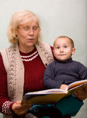 Grandmom reading to her grandson from a book — Stock Photo