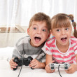 Happy girl and boy playing a video game — Stock Photo #6758772