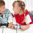 Stock Photo: Happy girl and boy playing a video game