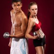 Strong young man and woman with dumbbells — Stock Photo