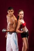 Silný mladý muž a žena s činkami — Stock fotografie