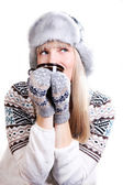 Beautifu woman in fur hat with a cup — Stock Photo