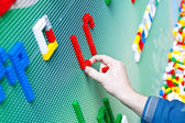 Child playing with plastic toy bricks — Stock Photo