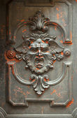 Monstrous face carved in a door — Stock Photo