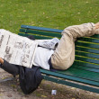 Reads a newspaper lying on a bench — Stock Photo