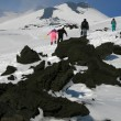 Walking on Etna Volcano covered by snow - Stock Photo