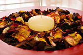 Candle in flower's petals — Stock Photo