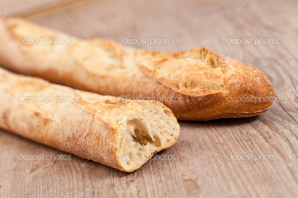 Fresh crusty baguette on wooden background — Stock Photo #6954527