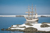 Sailing ship among the icebergs — Stock Photo