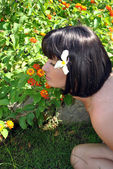 Woman sniffs the flowerses. — Stock Photo