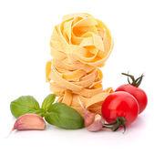 Italian pasta fettuccine nest and cherry tomato — Stock Photo