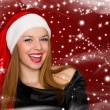 Portrait of beautiful sexy woman in a santa hat on red backgroun — Stock Photo
