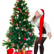 Smiling happy woman near a Christmas tree. Isolated over white b — Stock Photo