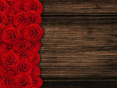 Roses at wooden background — Stock Photo